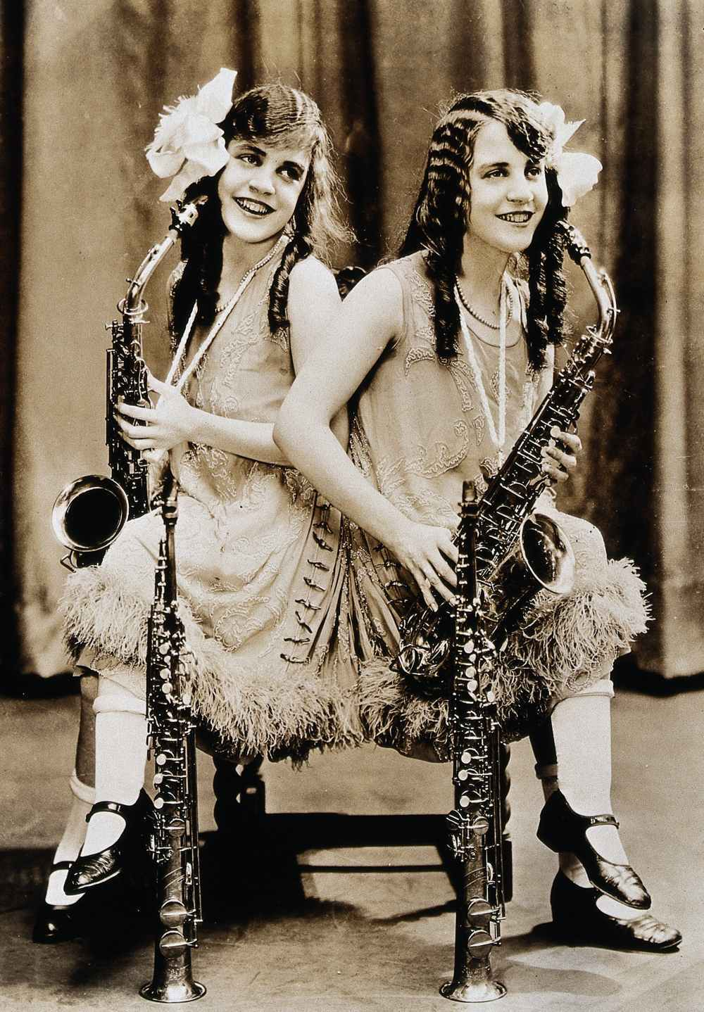 Daisy and Violet Hilton, conjoined twins, with saxophones
