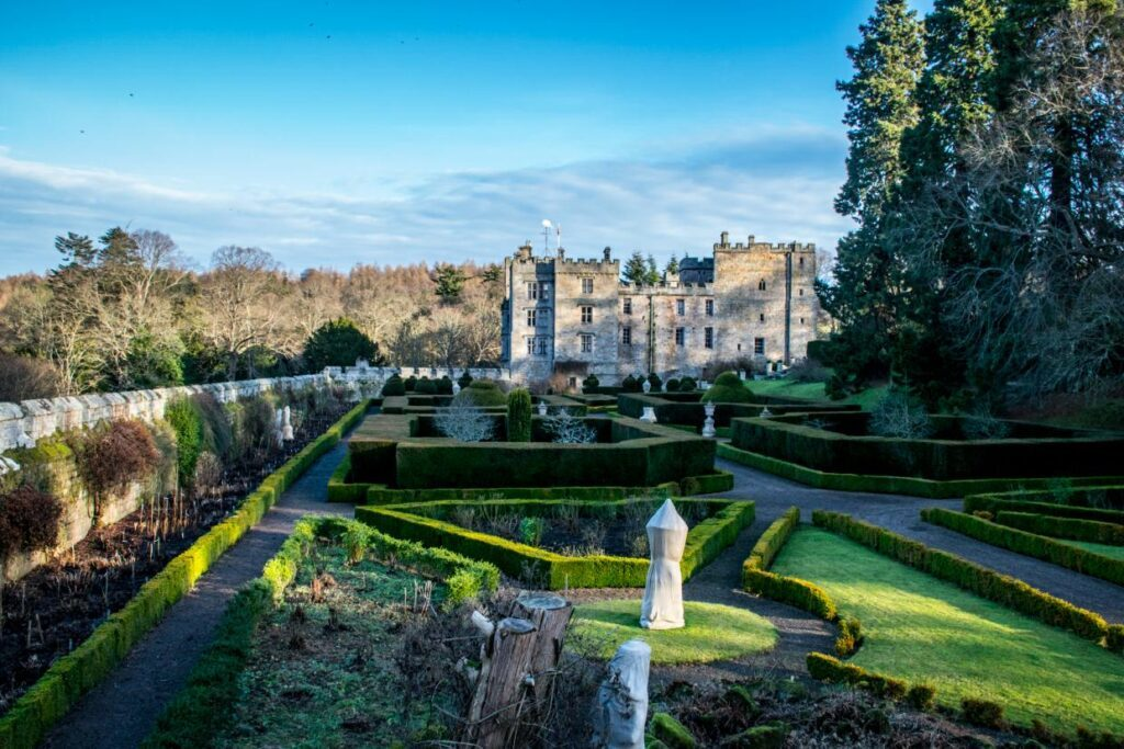 The west front of Chillingham Castle, viewed across the castle's Italian Garden.
