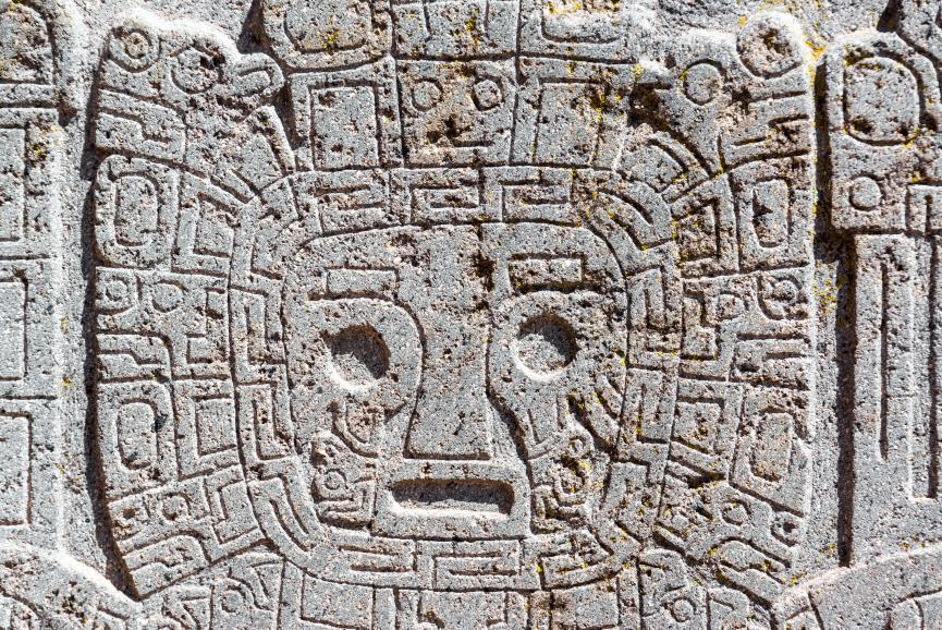"""The gateway god: Closeup view of a face carving at the Tiwanaku ruins near La Paz, Bolivia. It seems undeniable that the Tiwanaku artists viewed their gateway god as a fish (fish symbols are everywhere) perhaps in the sense of a creature breathing inside a water-filled helmet. Archaeologists refer to the gateway god as the """"crying"""" god, but rather than tears they are likely looking at bubbles. © Image Credit: Jesse Kraft 